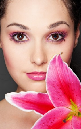 close-up portrait of beautiful woman with pink lily photo