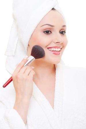 mujer maquillandose: joven y bella mujer aplicar maquillaje sobre fondo blanco  Foto de archivo