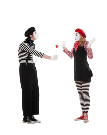 portrait of mimes. man giving small red heart to amazed woman. isolated on white background  photo