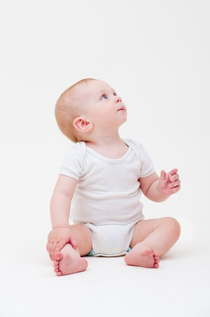 sit up: nice baby in white t-shirt sitting on the floor and looking up