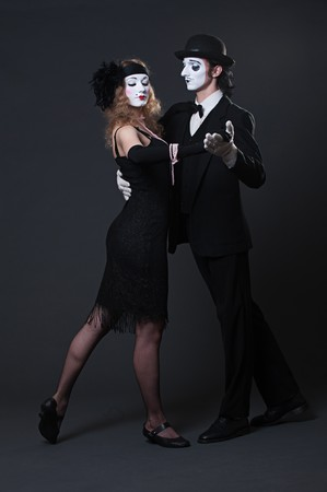 serious mimes dancing over dark background. retro style photo