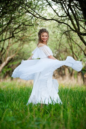 beautiful young woman in white dress is whirling  photo