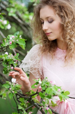 attractive young woman looking at small flower on tree photo