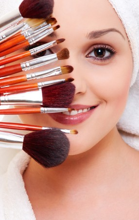 portrait of beautiful woman with brushes for make-up photo