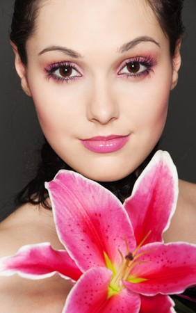 portrait of young attractive woman with pink lily photo
