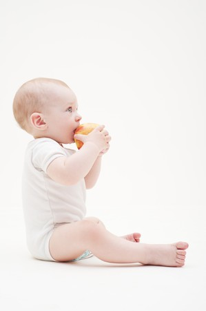 sitting on floor: sideview portrait of baby with yellow apple