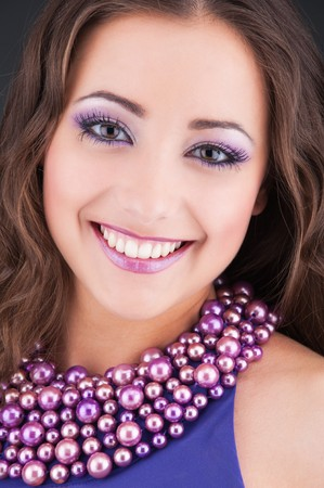 portrait of beautiful smiley woman in purple dress with beads  photo