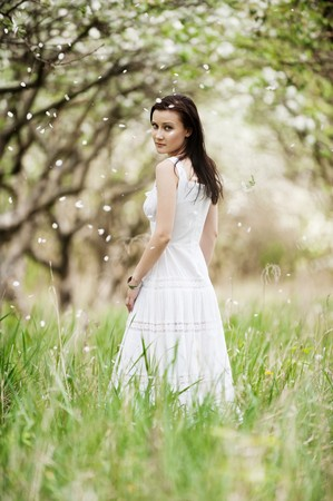 portrait of beautiful young woman in white dress walking in park  photo