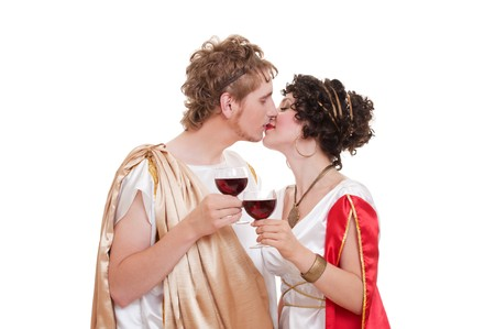 portrait of kissing couple with glasses of wine. greek style photo