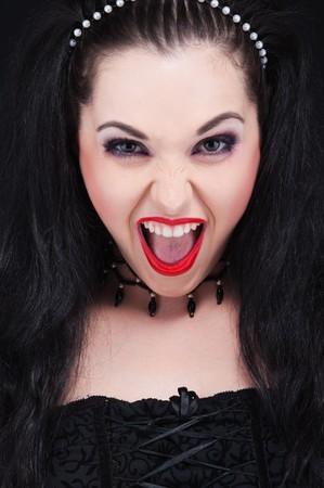 close-up portrait of emotional brunette over black background  photo