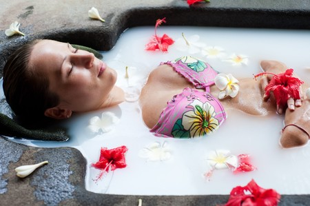 remedial: pretty woman relaxing in milk bath with flowers