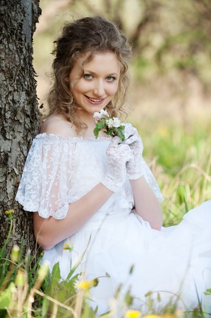 portrait of pretty woman with flower in park  photo