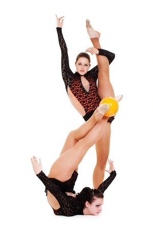 two pretty gymnasts posing with yellow ball. isolated on white background