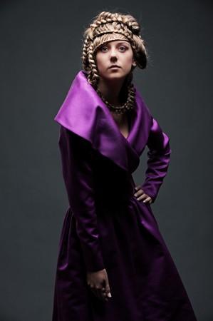portrait of attractive woman in violet dress over dark background  photo