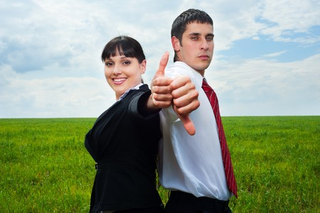 smiley businesswoman showing thumbs up and businessman showing thumbs down photo