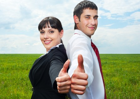 smiley businesspeople showing thumbs up over green grass and blue sky