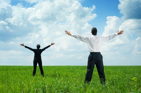 happy businesspeople standing on green grass and looking up photo