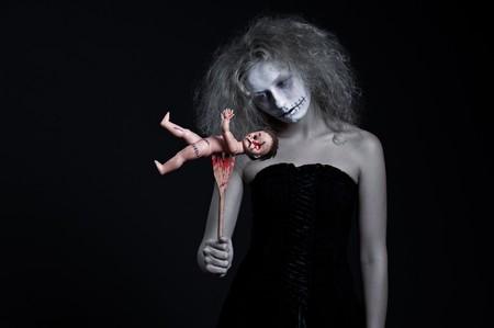 Portrait de fantôme avec poupée sanglante sur fond noir  Banque d'images