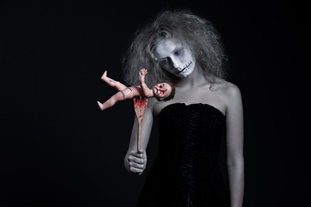 terrific: portrait of ghost with bloody doll over black background
