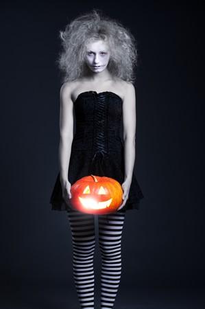 portrait of ghost with orange pumpkin over dark background photo