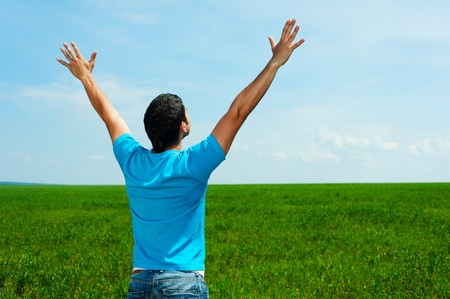 happy man in blue t-shirt standing on green meadow  Stock Photo