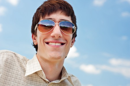 portrait of happy man in sunglasses against blue sky photo