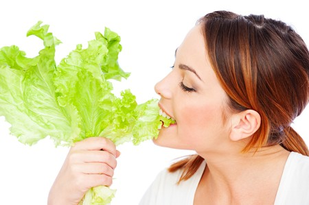 healthy young woman eating green lettuce over white background Stock Photo - 8129755