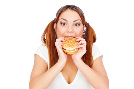pretty woman eating burger with gusto. isolated on white photo