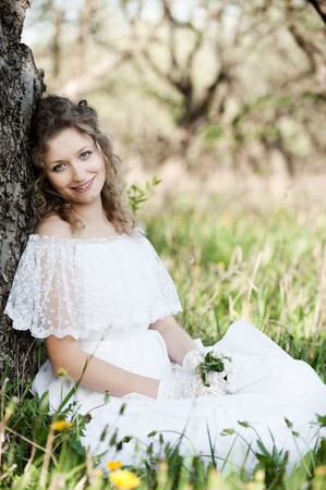 portrait of pretty woman in white dress sitting on the grass photo