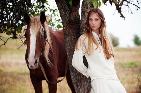 horse blonde: outdoor portrait of pretty woman with brown horse