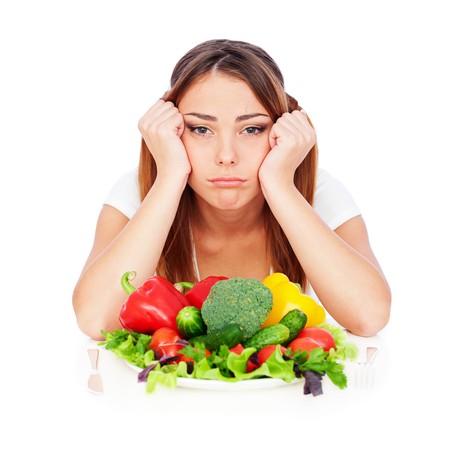 triste mujer sentada cerca de la placa con verduras y cansados de dieta