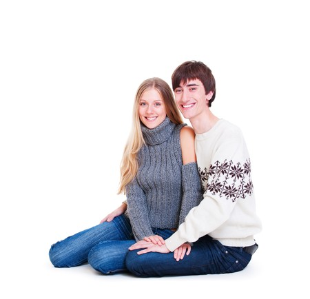 smiley happy couple sitting on the floor. isolated on white background photo