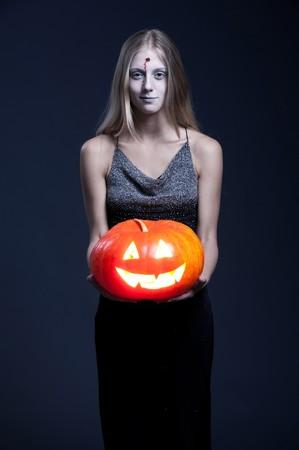 demoniacal: portrait of smiley zombie with orange pumpkin. halloween theme Stock Photo