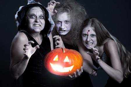 three angry ghost with orange pumpkin over dark background. halloween theme photo
