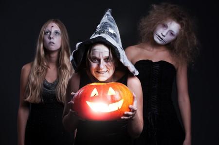 portrait of three halloween personages with orange pumpkin over dark background  photo