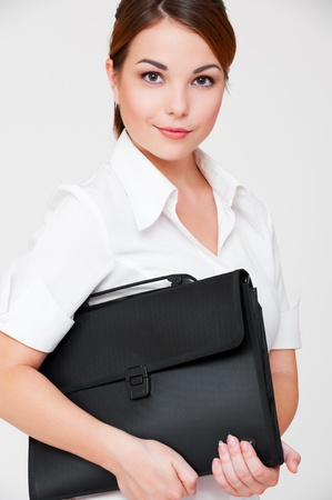 assured: portrait of assured businesswoman with briefcase folder over grey background
