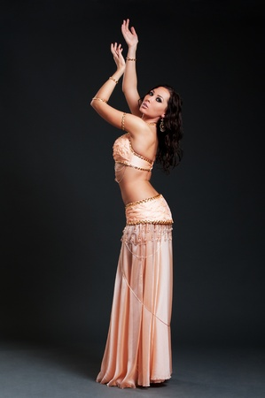 belly dance: attractive woman dancing belly dance over black background