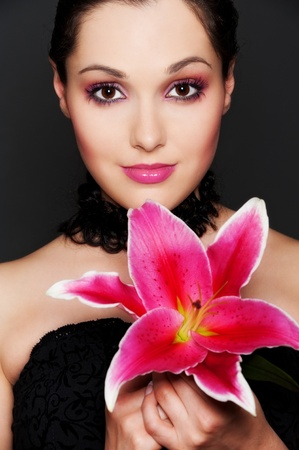 portrait of attractive woman with pink flower over dark background photo