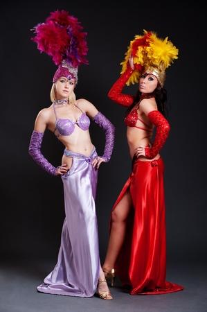 beautiful cabaret women in bright costumes posing over dark background