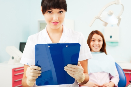 portrait of pretty smiley doctor with patient at dentists office photo