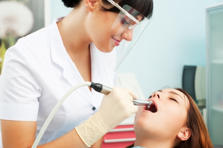 hygienist: portrait of smiley dentist in mask and patient
