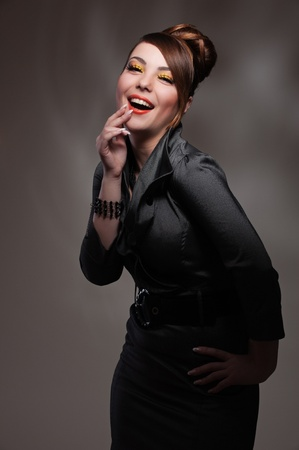 portrait of laughing young woman over dark background photo