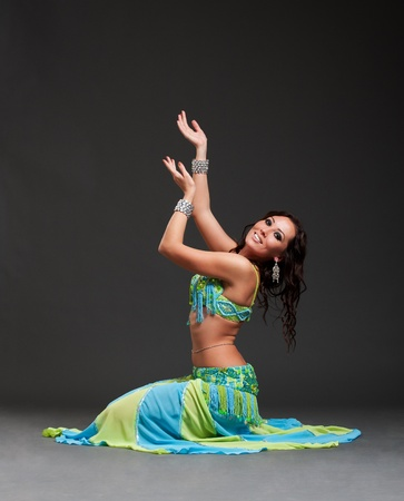 belly dance: beautiful oriental dancer posing over black background