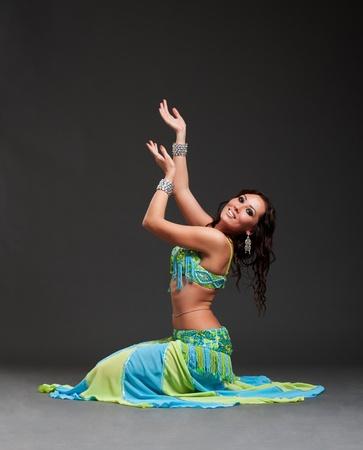 vientre femenino: bella bailarina oriental posando sobre fondo negro