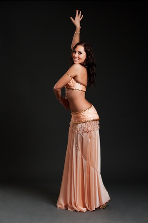 attractive woman dancing belly dance over black background  photo