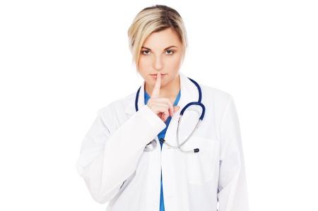 quiet adult: medico serio facendo segno di silenzio su sfondo grigio