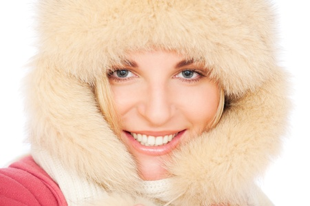 portrait of smiley woman in fur hat over white background photo