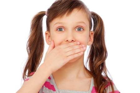 portrait of amazed small girl covering her mouth over white background  photo
