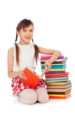 portrait of smiley schoolgirl sitting near books photo