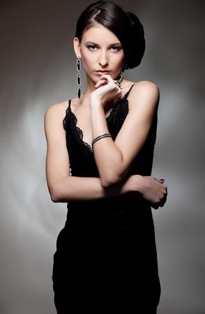 portrait of sexy slim woman in black dress over dark background photo